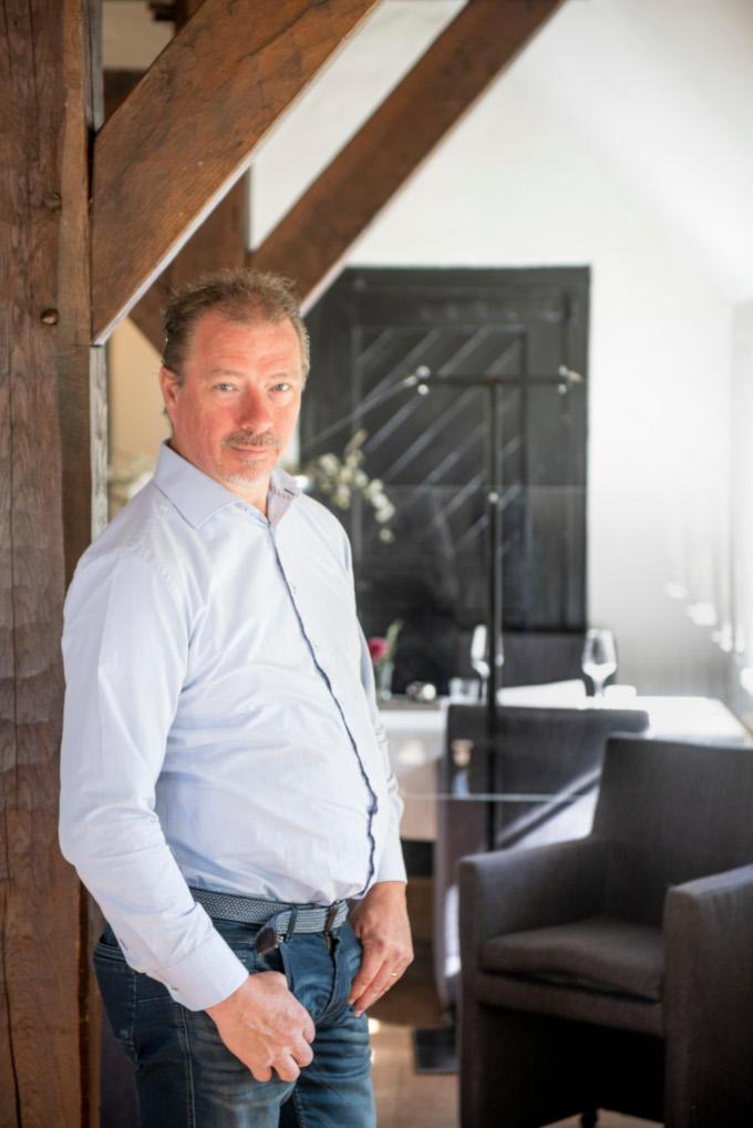 Hij is klaar voor heropening, zegt restauranthouder Arno Huisken. Achter hem is nog net de plexiglas plaat te zien. Die heeft hij geplaatst om gasten veilig te kunnen laten dineren.