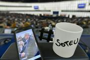 """A smartphone showing a photograph of Jean-Claude Juncker, next to white mug with the black inscription """"SOTEU"""" (State of the Union) on it, and with a # (hashtag) handle"""