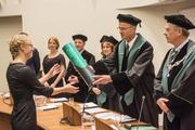 Vrouw krijgt bul uitgereikt van hoogleraar bij haar promotie